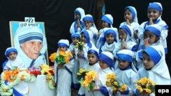 Девочки, одетые как Мать Тереза, у ее портрета в 2014 году – в 104-ю годовщину со дня рождения монахини