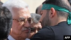 Palestinian President Mahmud Abbas (left) welcomes a prisoner wearing a Hamas headband following the release of hundreds of prisoners from Israeli jails in October.