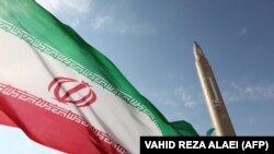 An Iranian flag flies at an undisclosed location in the Islamic republic next to a surface-to-surface Qiam-1 missile. (file photo)
