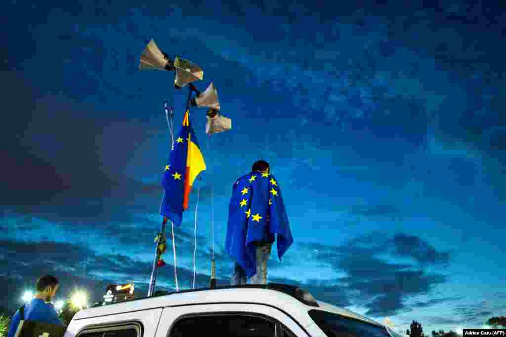 A man stands on a truck draped in an EU flag as demonstrators gather in front of the Romanian prime minister's office at an anticorruption rally in Bucharest. (AFP/Adrian Catu)