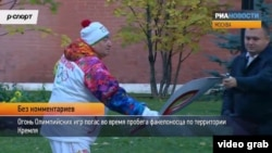 Russian Olympic torchbearer Shavarsh Karapetyan gets help relighting the torch after it flickered out at the Kremlin in Moscow on October 6.
