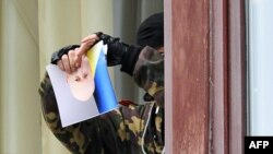 A pro-Russian activist rips a photo of interim President Oleksandr Turchynov as he stands at a window of the regional administration building in Luhansk.