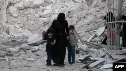 A Syrian family leaves the area following a reported air strike on the Al-Muasalat area in the northern Syrian city of Aleppo on September 23.