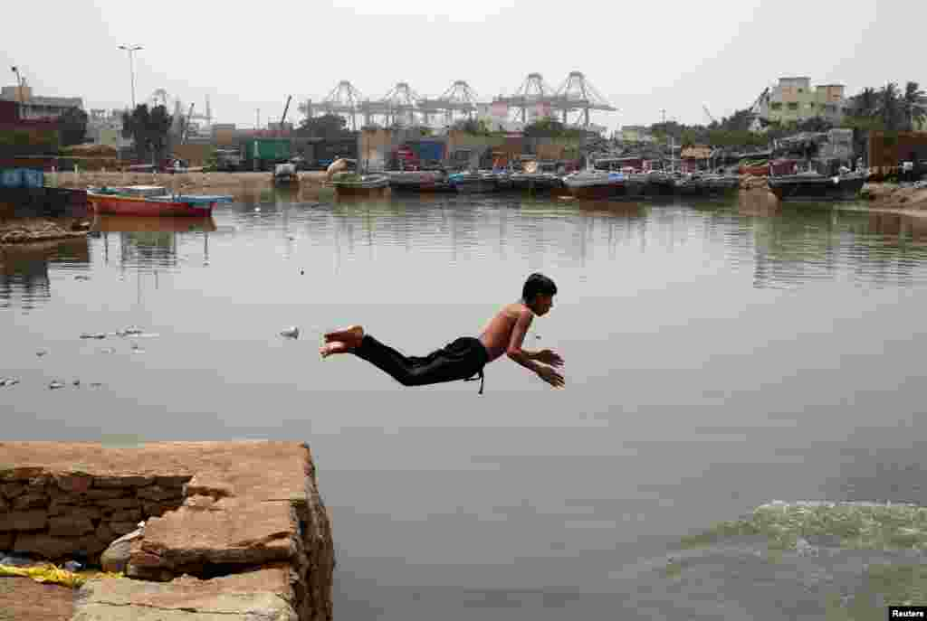 A Pakistani boy jumps into water to cool off during hot and humid weather at a port area in Karachi on May 3. (Reuters/Akhtar Soomro)