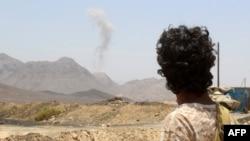 Një person i armatosur duke e shikur tymin nga përleshjet në Jemen