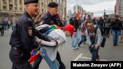 Police detain an LGBT activist during a protest in Moscow on August 26.