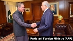 Pakistani Foreign Minister Shah Mahmood Qureshi (left) greets U.S. Special Representative for Afghanistan Zalmay Khalilzad in Islamabad on April 5.