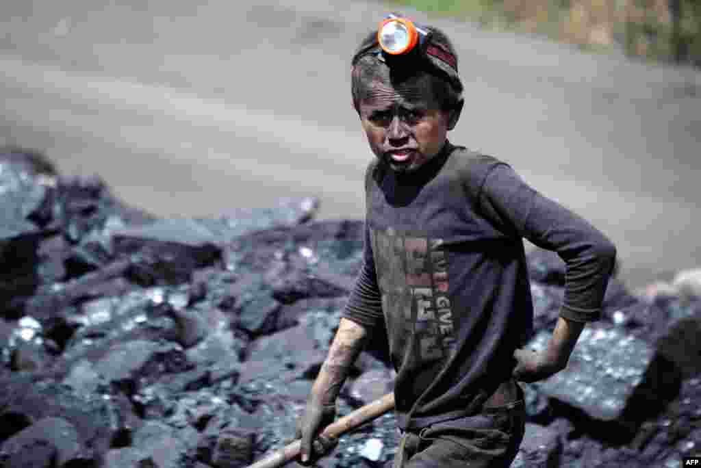 An Afghan child looks on as he works at a coal mine which collapsed on April 30, killing some 40 miners and trapping an unknown number of others in the Dar-i-Suf district of Samangan Province. (AFP/Farshad Usyan)