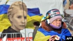 Участница антиправительственных демонстраций в Киеве на фоне портрета Юлии Тимошенко, 30 января 2014 года.