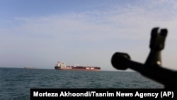 A speedboat of Iran's Revolutionary Guard trains a weapon toward the British-flagged oil tanker Stena Impero, which was seized in the Strait of Hormuz on Friday by the Guard, in the Iranian port of Bandar Abbas, July 21, 2019