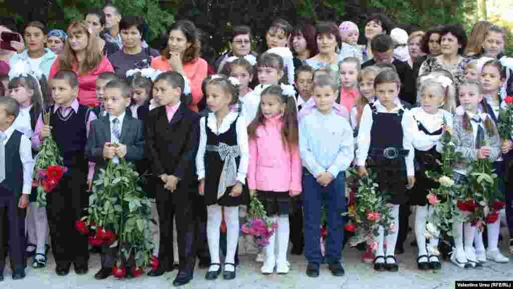 Children carry roses in Balanesti, Moldova.