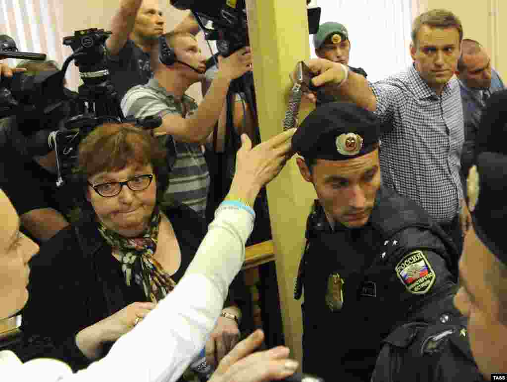 Aleksei Navalny passes his watch and phone to his wife as he is led away in handcuffs.