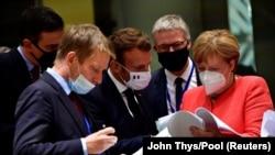 Președintele francez Emmanuel Macron (centru) și cancelara germană Angela Merkel, la primul summit pe viu după carantina din primăvară. Bruxelles, 20 iulie 2020.