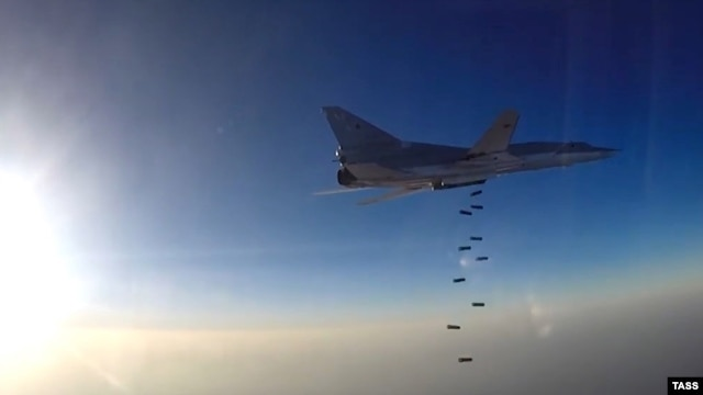 A still image taken from video footage and released by Russia's Defense Ministry on August 14 shows a Tu-22M3 dropping bombs near what the ministry said is the city of Deir ez-Zor, Syria.