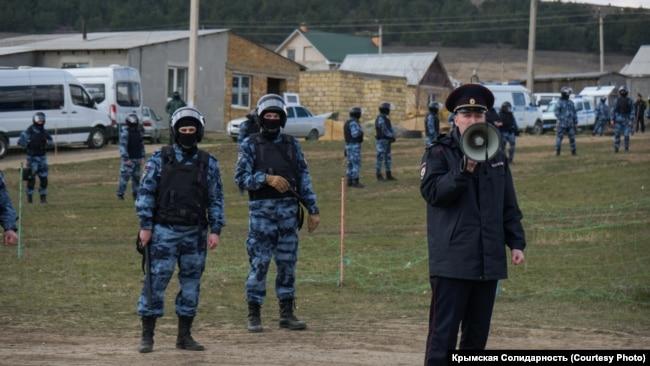Российские силовики стоят в оцеплении в поселке компактного проживания крымских татар. Крым, 27 марта 2019 года