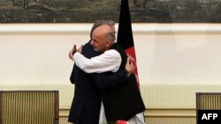 Afghanistan -- Presidential candidates Abdullah Abdullah and Ashraf Ghani Ahmadzai (front) embrace after signing a power-sharing agreement at the Presidential Palace in Kabul, September 21, 2014