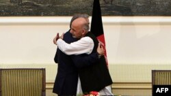 Abdullah Abdullah and Ashraf Ghani embrace after signing a power-sharing agreement at the Presidential Palace in Kabul, September 21, 2014.