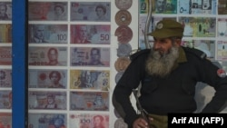 FILE: A security guard sits outside the currency exchange shop in the eastern Pakistani city of Lahore.