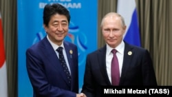 Russian President Vladimir Putin (right) and Japanese Prime Minister Shinzo Abe meet at a summit in Vietnam last year.