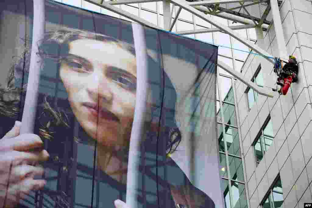 "Members of Greenpeace hang a large poster of Dutch activist Faiza Oulahsen on the office building of Shell during a protest calling for the release of the ""Arctic 30"" in Rotterdam on November 21. Oulahsen was one of 30 people from 18 countries who were arrested after a protest in September at a Gazprom oil rig in the Arctic. (AFP/Martijn Beekham)"