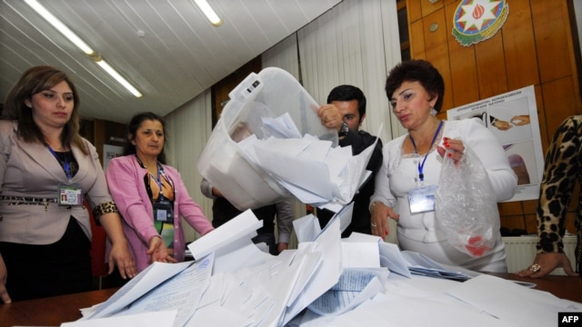 Azerbaijani election officials empty ballot boxes at a polling station in Baku on October 9.