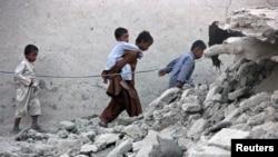 Пакистанцы идут мимо руин жилого дома в районе Аваран провинции Белуджистан. 25 сентября 2013 года.