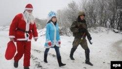 Волонтери переодягнені у костюми Діда Мороза та Снігуроньки разом з українським військовослужбовцем біля Лисичанська. Січень 2015 року. Ілюстраційне фото