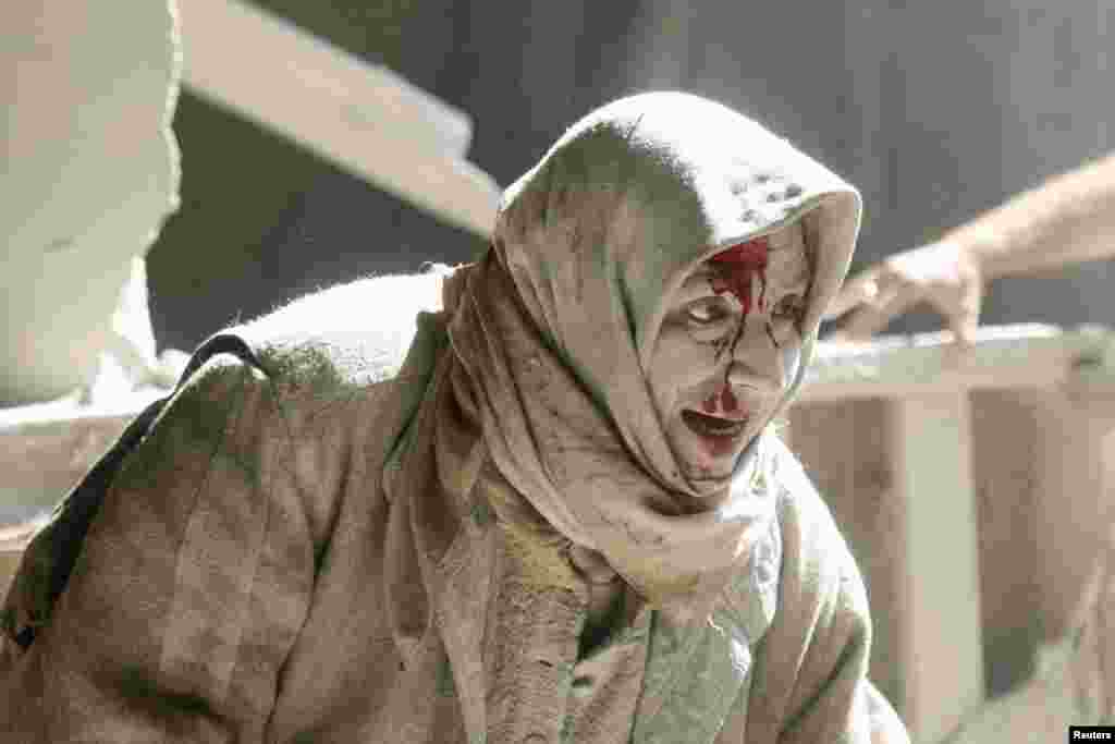 An injured woman reacts at a site hit by air strikes in the rebel-held area of Old Aleppo, Syria. (Reuters/Abdalrhman Ismail)