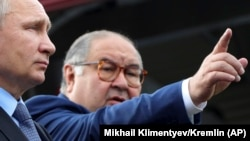 Uzbek-born Russian businessman Alisher Usmanov (right) has been included on a list of people with close links to President Vladimir Putin (left) who may be the subject of future U.S. sanctions. (file photo)