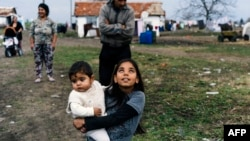 A Romany girl carries her brother on a street in the Bulgarian village of Ekzarh Antimovo.