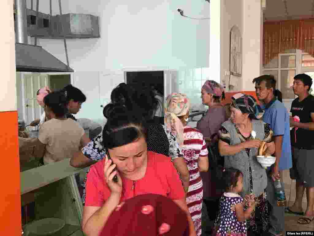 Люди в очереди за едой в столовой эвакуационного пункта при школе № 87 города Шымкента.