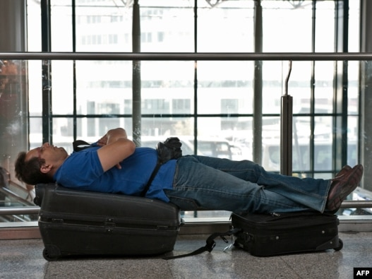 Italy - A passenger rests on his suitcases at Fiumicino airport near Rome, 19Apr2010