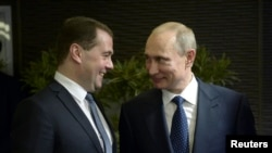 Russia -- Russia's President Vladimir Putin (R) talks to Prime Minister Dmitry Medvedev before the opening ceremony of the 2014 Paralympic Winter Games in Sochi, March 7, 2014.