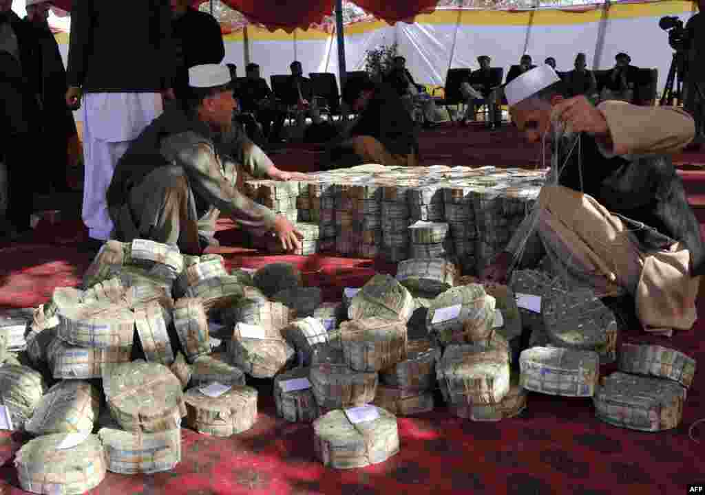 Afghan officials count and adjust bundles of the Afghan currency, the afghan, before setting the notes on fire in Jalalabad, in Nangarhar Province. (AFP/Noorullah Shirzada)