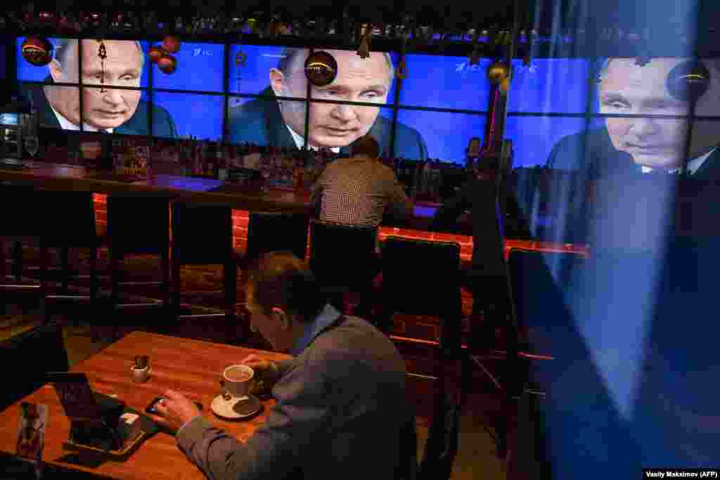 A man drinks coffee in front of screens broadcasting Russian President Vladimir Putin's annual press conference, at a bar in Moscow on December 20. (AFP/Vasily Maksimov)