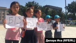 Дети гражданского активиста Нуржана Мухаммедова, заявляющего о давлении со стороны полиции, на акции протеста у здания городского акимата. Шымкент, 10 июля 2018 года.