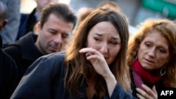 Mourners on November 15 look on at a memorial site outside of the Le Belle Equipe restaurant, in the 11th district of Paris, for victims of the November 13 terrorist attacks in Paris.