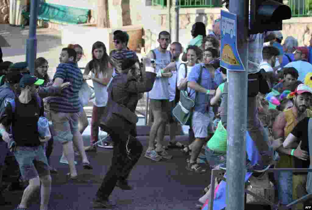 Yishai Shlissel (center), an ultraorthodox Jew, raises a knife as he sets about stabbing six people taking part in a gay pride parade in central Jerusalem, Israel, on July 30. (AFP/Kobi Schutz)