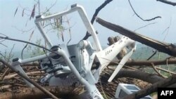 A photo purportedly shows the wreckage of a small lightweight model drone of a type widely available for commercial purchase, lying on branches of wood near Bhimber, a district of Pakistani-administered Kashmir on July 15.