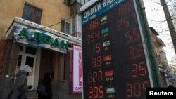 Люди проходят рядом с пунктом обмена валют в Алматы. 11 февраля 2014 года.