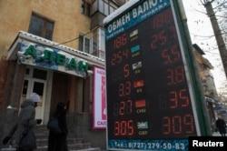 Алматыдағы ақша айырбастайтын орындардың бірінің қасынан өтіп жатқан адамдар. 11 ақпан 2014 жыл.