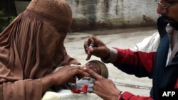A Pakistani health worker administers polio drops to a child during a polio vaccination campaign in Peshawar on March 3.