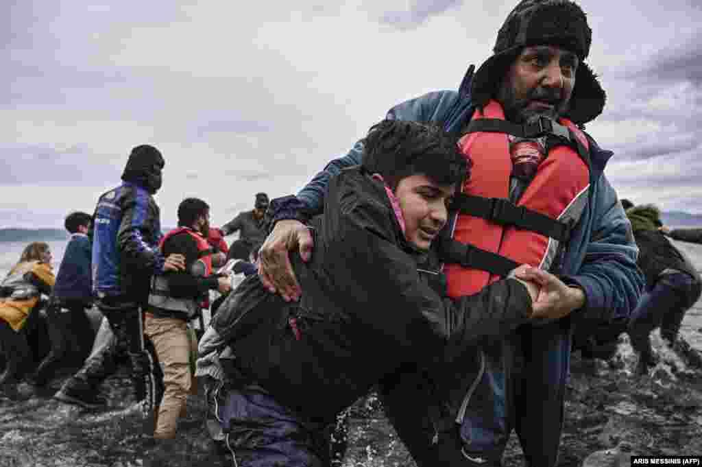 Мужчина помогает идти ребенку после того, как их шлюпка, в которой находились 54 афганских мигранта, прибыла на остров Лесбос, 28 февраля 2020 года.
