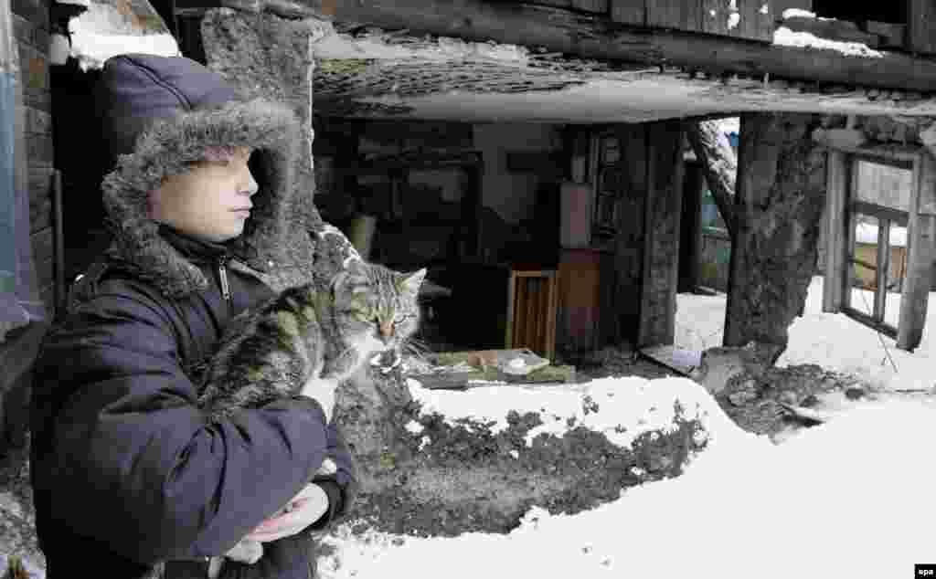 A local boy holds a cat outside his Donetsk home, which was damaged by shelling.