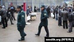 Сотрудники узбекской милиции идут по местному рынку.