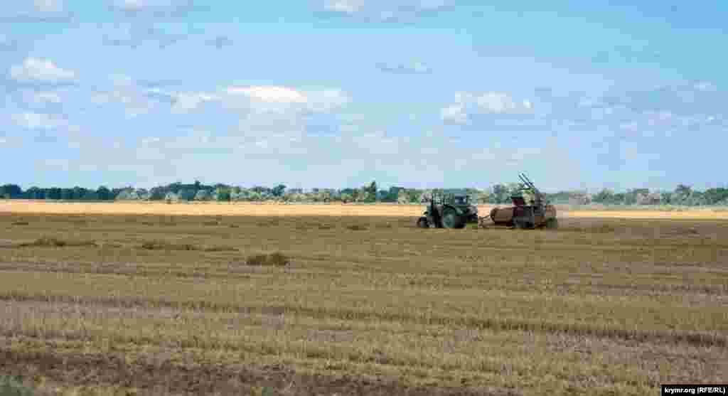 На другом поле трактор тюкует солому