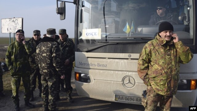 OSCE military observers talk on the phone as they wait at the Chongar checkpoint blocking the entrance to Crimea on March 7.