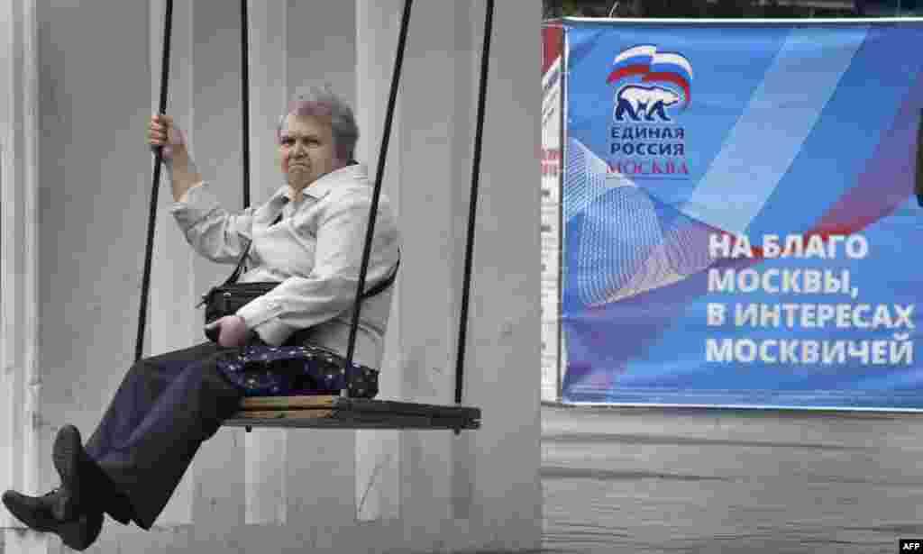 Žena na ljuljački uz izborni plakat Ujedinjene Rusije u centru Moskve uoči parlamentarnih izbora u toj zemlji, zakazanih za 18. septembar. (AFP/Aleksander Nemenov)