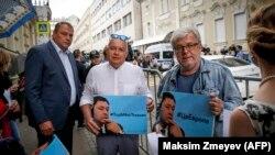 Russia Today (RT) kanalının rəhbəri Dmitry Kiselyov (ortada) Kirill Vyshinsky-nin fotosu olan plakat tutub. Jurnalist mayın mayın 18-də Moskvadakı Ukrayna səfirliyi qarşısında saxlanmışdı