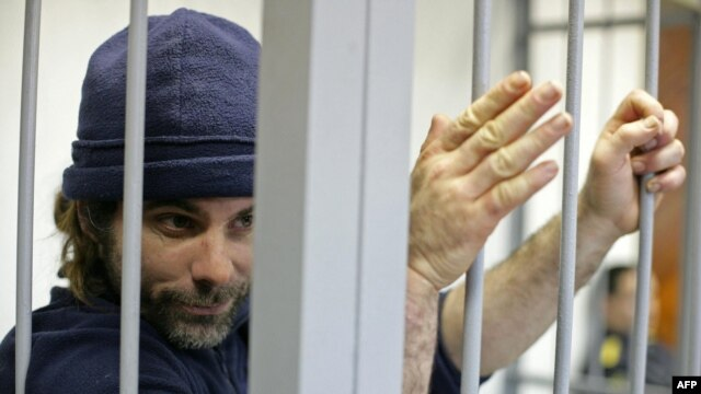 British Greenpeace International activist Iain Rogers holds the bars of a cell during his bail hearing in Russia on October 22.